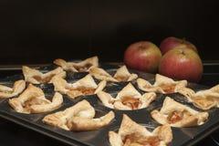 Las galletas cocidas llenaron de las rebanadas de manzanas rojas, cubiertas con el azúcar de formación de hielo y canela y las ma Imagen de archivo
