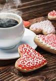 Las galletas cocieron en día de tarjetas del día de San Valentín y una taza de café Foto de archivo libre de regalías