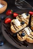 Las galletas con los arándanos, fresas, azotaron la salsa de la crema y de chocolate Fotografía de archivo libre de regalías