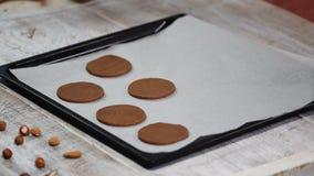 Las galletas crudas puestas del chocolate en una bandeja que cuece con el papel de pergamino, alistan para cuecen almacen de metraje de vídeo