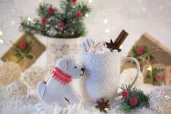 Las galletas de la Navidad con la decoración festiva en la forma de un perro y de una taza blanca de la Navidad picante caliente  Imagen de archivo libre de regalías