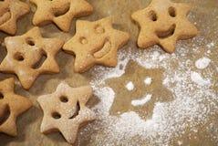 Las galletas de la Navidad con un plano de la cara de la sonrisa ponen en el papel que cuece fotografía de archivo libre de regalías