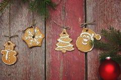 Las galletas de la Navidad cuelgan cerca de una pared de madera roja, ramas del abeto con las decoraciones de la Navidad Fotos de archivo libres de regalías