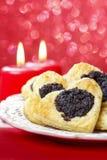 Las galletas de la semilla de amapola en corazón forman en la tabla Imagen de archivo libre de regalías