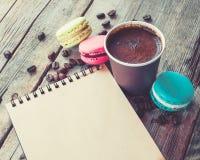 Las galletas de los macarrones, la taza de café del café express y el bosquejo reservan Imágenes de archivo libres de regalías