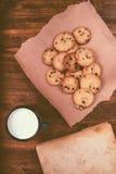 Las galletas de microprocesador de chocolate, la taza de la leche y el vintage hechos en casa reservan imagen de archivo libre de regalías