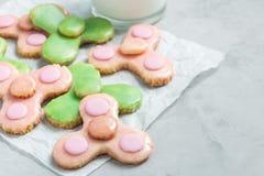 Las galletas de torta dulce hechas en casa hechas en forma de moda del juguete del hilandero y el vidrio de leche, horizontales,  Foto de archivo