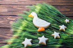 Las galletas del pan de jengibre formaron el pato y las estrellas con el oído del trigo en un fondo de madera Profundidad del cam imagen de archivo libre de regalías