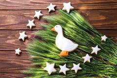 Las galletas del pan de jengibre formaron el pato y las estrellas con el oído del trigo en un fondo de madera Profundidad del cam Foto de archivo
