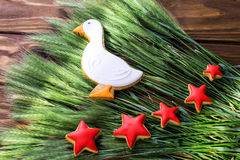Las galletas del pan de jengibre formaron las estrellas del pato y del rojo con el oído del trigo en un fondo de madera Profundid Imagenes de archivo