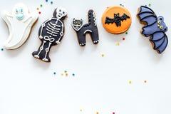 Las galletas del pan de jengibre de Halloween con las imágenes golpean, el esqueleto, fantasma en el copyspace blanco de la opini Imágenes de archivo libres de regalías