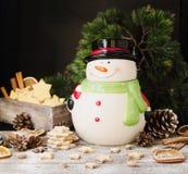 Las galletas del pan de jengibre de la Navidad protagonizan con un tarro del muñeco de nieve en una tabla de madera, foco selecti Fotografía de archivo