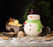 Las galletas del pan de jengibre de la Navidad protagonizan con un tarro del muñeco de nieve en una tabla de madera, foco selecti Fotos de archivo libres de regalías