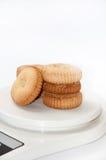 Las galletas del té arreglaron en una escala digital medir Foto de archivo libre de regalías