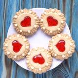 Las galletas dulces de la jalea con el relleno rojo les gusta un corazón en la placa en fondo de madera azul esmeralda Fotografía de archivo libre de regalías