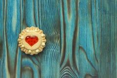 Las galletas dulces de la jalea con el relleno rojo les gusta un corazón en la tabla de madera azul Imagenes de archivo