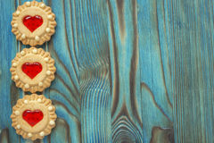 Las galletas dulces de la jalea con el relleno rojo les gusta un corazón en la tabla de madera azul Fotos de archivo libres de regalías