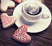 Las galletas en forma de corazón cocieron en día de tarjetas del día de San Valentín y una taza de café Foto de archivo libre de regalías