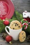 Las galletas hechas en casa con las gotas de chocolate para el banquete de Santa Claus en el Año Nuevo rodeada por el abeto ramif Imagenes de archivo