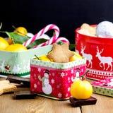 Las galletas hechas en casa del pan de jengibre de la Navidad en la Navidad de madera del fondo tratan el caramelo cambiante de l Imagen de archivo