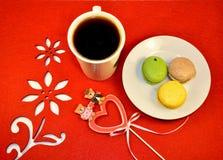 Las galletas multicoloras de los macarrones, la taza de café y el corazón firman en la servilleta roja brillante con las flores Foto de archivo