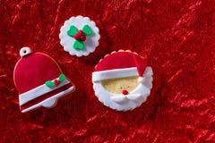 Las galletas Papá Noel de la Navidad hacen frente y campana de Navidad en fondo rojo Imagen de archivo