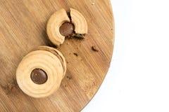Las galletas quebradizas de la endecha plana remataron con crema del chocolate en el tablero de madera Foto de archivo