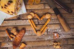 Las galletas se apelmazan en la D de la tarjeta del día de San Valentín en forma de corazón rústica del tablero marrón Imágenes de archivo libres de regalías
