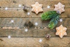 Las galletas y el abeto del pan de jengibre ramifican en fondo de madera con los copos de nieve con el espacio para su texto foto de archivo