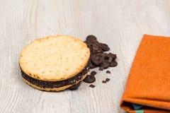 Las galletas y la toalla del chocolate en la tabla Foto de archivo libre de regalías