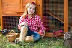 Las gallinas del criador embroman al granjero del ranchero de la muchacha con los polluelos en gallinero de pollo foto de archivo