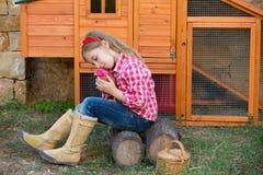 Las gallinas del criador embroman al granjero del ranchero de la muchacha con los polluelos en gallinero de pollo fotografía de archivo