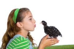 Las gallinas del criador embroman al granjero del ranchero de la muchacha que besa un polluelo del pollo imagen de archivo libre de regalías