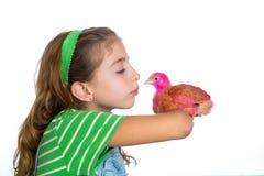 Las gallinas del criador embroman al granjero del ranchero de la muchacha que besa un polluelo del pollo Foto de archivo libre de regalías