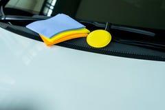Las gamuzas de los limpiadores muchos colorean el paño y la cera amarilla de la esponja con el coche blanco Imagen de archivo