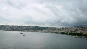 Las gaviotas comunes que vuelan en mediterráneo ven con Nápoles en fondo metrajes