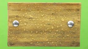 Las gotas de agua caen en un marco de madera, aislado en verde almacen de video
