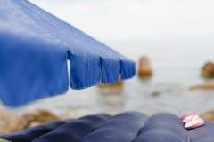 Las gotas de agua de la lluvia fluyen abajo del parasol de playa Foto de archivo libre de regalías