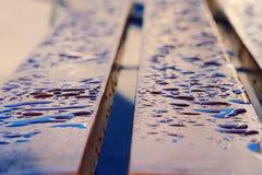 Las gotas de agua en el banco de madera fotos de archivo