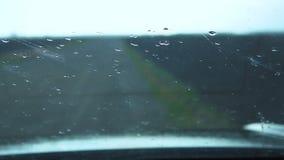 Las gotas de agua en el parabrisas del coche almacen de video