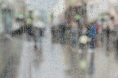 Las gotas de agua en el vidrio de la ventana, gente caminan en el camino en el día lluvioso, fondo borroso del extracto del movim Imagenes de archivo