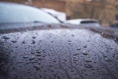 Las gotas de agua en la pintura del coche con suavidad empañaron el fondo Foto de archivo