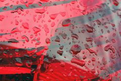 las gotas de agua en las linternas rojas, pies del coche se cierran para arriba fotos de archivo libres de regalías