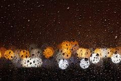 Las gotas de agua fluyen abajo del vidrio de la ventana en la noche Imagen de archivo libre de regalías