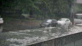 Las gotas de la lluvia caen en el encintado, coches en el fondo, concepto del tiempo, concepto urbano almacen de video