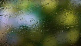 Las gotas de la lluvia corridas abajo del vidrio, las ramas de un árbol con las hojas verdes se están sacudiendo en un fondo borr metrajes