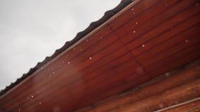 Las gotas de lluvia fluyen abajo maravillosamente con un tejado de madera Diversa estación