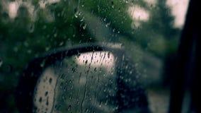Las gotas de lluvia fluyen abajo sobre un vidrio de ventanilla del coche, día lluvioso almacen de metraje de vídeo