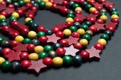 Las gotas decorativas de la Navidad de madera colorida arreglaron en un espiral en una superficie neutral Imágenes de archivo libres de regalías