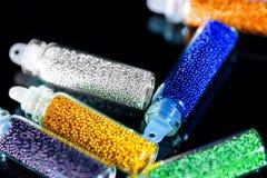 Las gotas multicoloras para el clavo diseñan en un fondo negro del espejo Imagen de archivo libre de regalías